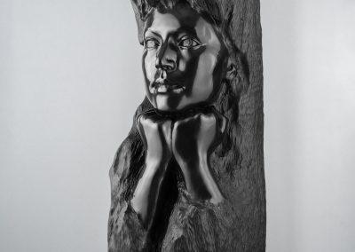 Pensativa - escultura femenina incrustada en un tronco en macryl negro